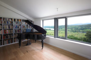 An open room with a bookshelf and a pianio. The windows look out to a field.