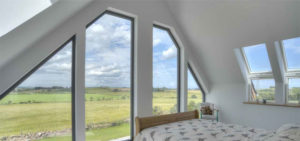 A bedroom with many windows looking out onto a green space