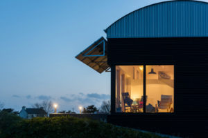 A home with large fixed glass windows, lit from within at dusk.